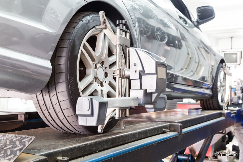 Closeup of tire clamped with aligner undergoing auto wheel align
