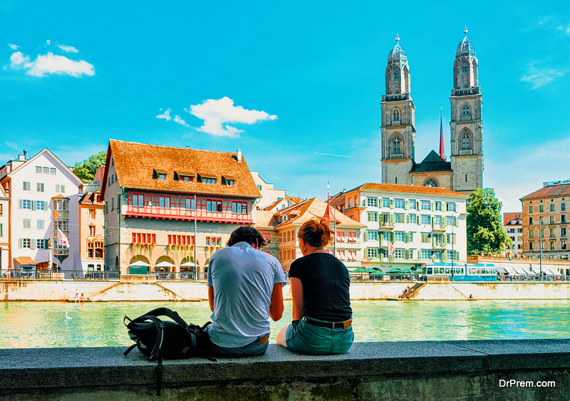 Young couple sitting at Limmatquai Grossmunster Church in Zurich