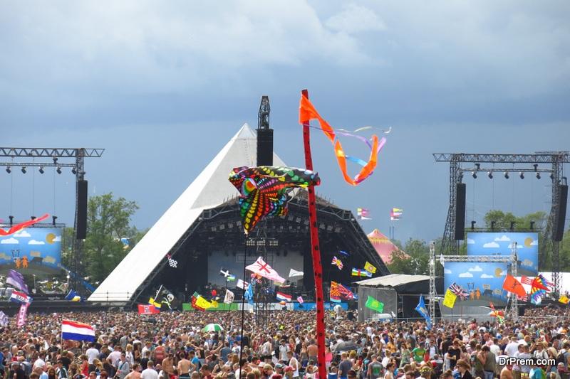Glastonbury Festival music festival Pyramid Stage crowds stormy sky