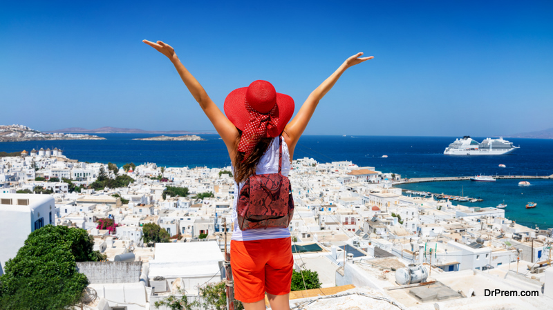 Traveler woman enjoys the view to the beautiful town of Mykonos island